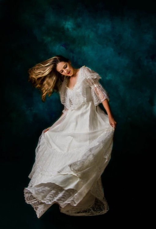 Bride with full length gown spinning in front of 'Old Masters' blue background.