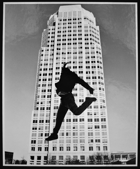Allison_Isley image of silhouette of person jumping in front of a tall office building.