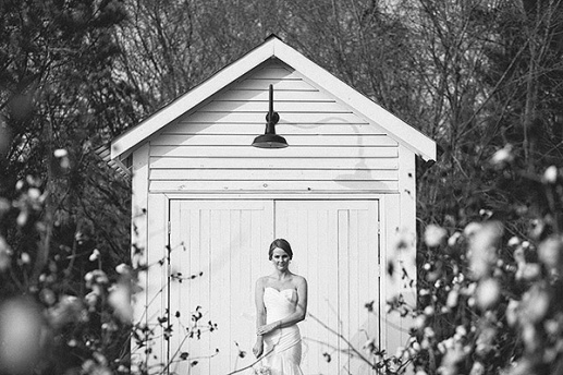 Bride standing in front of small white wooden building.