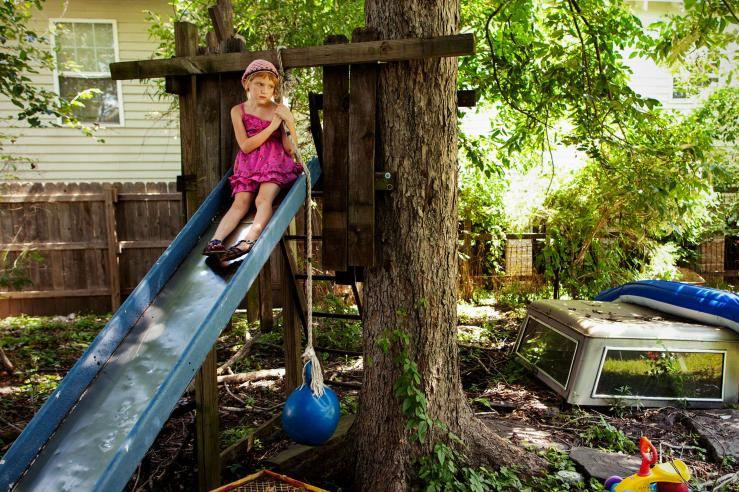 Girl on a slide overlooking a yard of rubble_01leadpoisoning.ngsversion.1439991294248.adapt.1900.2