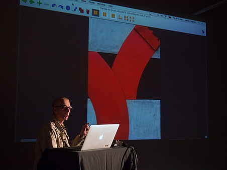 Burk Uzzle at a computer during a critique of projected student images.