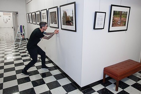 Ray Jones putting up image descriptions on gallery wall.
